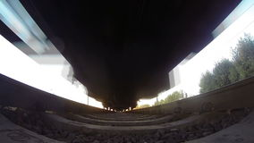 Train, view from below. Sunset. The camera on the sleepers under the train, view from below. sunset stock video