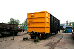 Train wagon. A yellow-black train cargo wagon in the factory Stock Photo