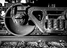 Train Wheels Black and White. Close view of train wheels and suspension in gritty black and white royalty free stock photography