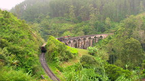 Train winding along the hillside & over bridge, Central Highlands. Sri Lanka stock footage