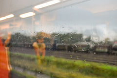 Through the train window. Outside the train window it is raining. Drops of water running down the glass. In the reflection of the glass you can see what is Stock Image