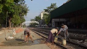 TRAIN WORKERS: Workers shovel cement and repair train platform. From ' Diesel Train in Myanmar  (Asia) ', one of many clips from this series from stock video footage