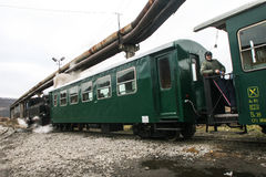 Train workshops with running bridge. Brad, Romania, December12, 2009: Tourists are travel in an old steamed cog train in Brad, on winter holydays Royalty Free Stock Photo
