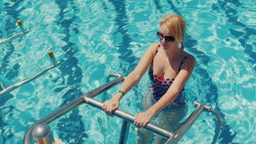 Train your body in the pool. A young woman in a swimsuit is escorting a training session in the pool on the simulator. Active and healthy lifestyle. 4K video stock video footage