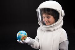 Trained astronaut is looking at globe in his hand stock images