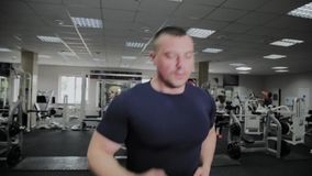 Trained man on a treadmill in a gym. Trained man on a treadmill in a gym stock video