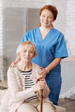 Trained private medical worker doing a weekly checkup. Medical services at home. Capable lovely neat doctor visiting her elderly patient and making sure she royalty free stock photo