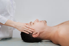 Trained skillful doctor conducting a therapeutic relaxing procedure. Pressing the right spots. Excellent qualified remarkable expert helping her patient calming stock photography