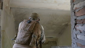 Trained soldiers searching floor to floor of ruined building then descending stairs for exit stock video footage