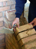 Trainee bricklayer. Positioning brick on wall support Stock Photography