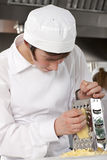 Trainee chef grating cheese in commercial kitchen Stock Photography