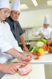 Trainee chef learning to tie joint meat Stock Images