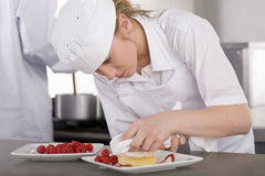 Trainee chef wiping plate of gourmet dessert in commercial kitchen Stock Image