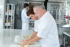 Trainee chef wiping plate gourmet dessert. Trainee chef wiping plate of gourmet dessert Stock Image