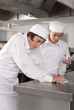 Trainee chefs cleaning work surface in commercial kitchen Stock Images