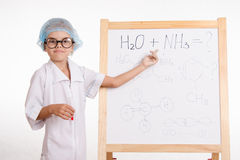 Trainee in chemistry class shows at the formulas on a blackboard Stock Photo