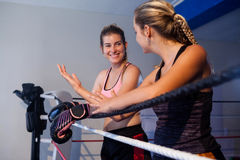 Trainee and coach interacting with each other. In boxing ring Stock Images