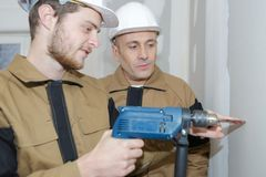 Trainee electrician learning trade stock photo