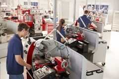 Trainee engineers operating equipment in a small factory royalty free stock images