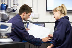 Trainee Engineers Studying Plans With CMM Arm In Foreground Royalty Free Stock Photography