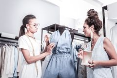 Dark-haired trainee wearing glasses working in famous successful atelier. Trainee in glasses. Dark-haired trainee wearing glasses and light white dress working stock image