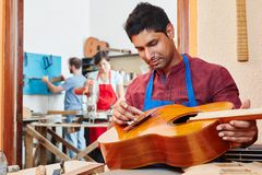 Trainee of guitar maker repairs guitar. At luthier`s shop Stock Photo