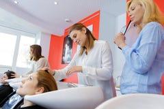 Trainee hairdresser washing clients hair under supervision. Trainee hairdresser washing a clients hair under supervision royalty free stock photo