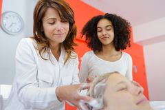 Trainee hairdresser washing female clients hair. Woman stock images
