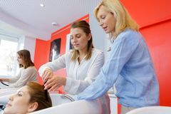 Trainee hairdresser washing female clients hair under supervision. Hairdresser royalty free stock image