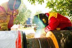 Trainee is with instructor using necessary welding equipment and. Welder working on a pipeline in construction site wearing overall and safety equipment Royalty Free Stock Photo