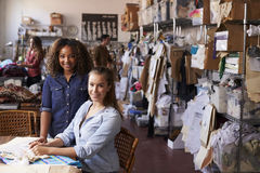 Trainee and manager at clothing design studio look to camera Royalty Free Stock Image