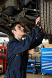 Trainee Mechanic Working Under Car Stock Photography