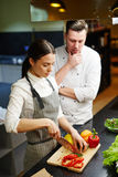 Trainee and mentor. Trainee preparing slow food under chef control Stock Image