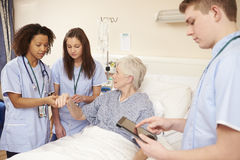 Trainee Nursing Staff By Female Patient's Bed In Hospital Stock Photos
