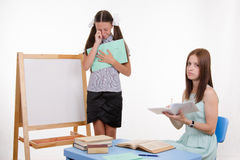 Trainee received low marks for not knowing lesson topic. Pupil stands at the blackboard, the teacher sits at his desk and listens to the student royalty free stock photo