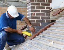Trainee roofer. Learning how to tile a roof properly Stock Photos