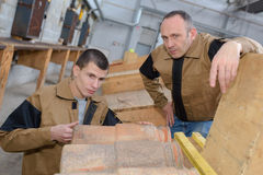 Trainee roofer learning how to tile roof properly Royalty Free Stock Photography