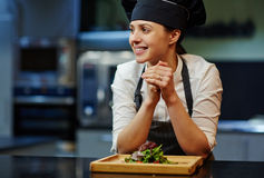 Trainee with salad. Happy young trainee in uniform by workplace Royalty Free Stock Photography