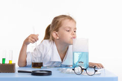 Trainee smelling liquid in chemistry class Stock Image