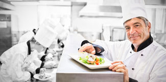 Trainees preparing dishes by head chef with salmon dish on counter. Trainees preparing dishes with head chef presenting salmon dish on counter Royalty Free Stock Photos