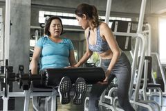 Trainer with asian senior woman lifting barbell in gym. healthy lifestyle and workout concept. Trainer with asian senior women lifting barbell in gym. healthy stock image