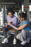 Trainer Assistance Senior Woman In Lifting Dumbbell At Gym. Full length of female trainer assistance senior women in lifting dumbbell at gym royalty free stock photography