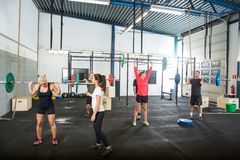 Trainer Assisting Athletes In Lifting Barbells Stock Image