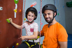 Trainer assisting boy in rock climbing at fitness studio stock photo