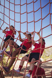Trainer assisting boy to climb a net during obstacle course training Stock Image