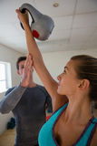 Trainer assisting female athlete in lifting kettlebells at club. Male trainer assisting female athlete in lifting kettlebells at club Stock Photography