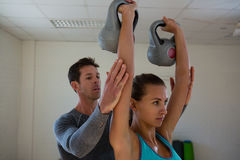 Trainer assisting female athlete in lifting kettlebells. At gym Stock Photo