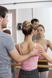Trainer Assisting Female Ballet Dancer In Dance Studio. Rear view of mid adult male trainer assisting female ballet dancer in dance studio Royalty Free Stock Photo