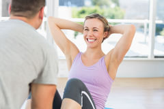 Trainer assisting fit woman in doing sits up. Male trainer assisting fit women in doing sits up in exercise room Royalty Free Stock Photos