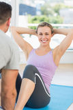 Trainer assisting fit woman in doing sits up Royalty Free Stock Image